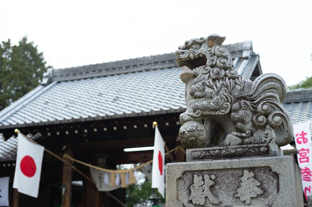 Komainu statue with shrine and flags behind.