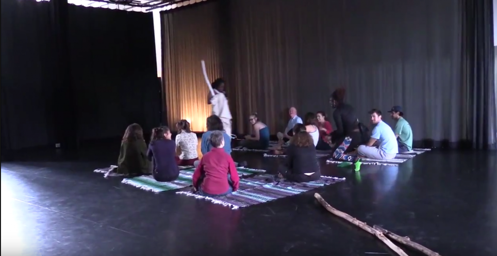 Audience sits on rugs in the center of dance studio, facing a performer holding a wooden staff