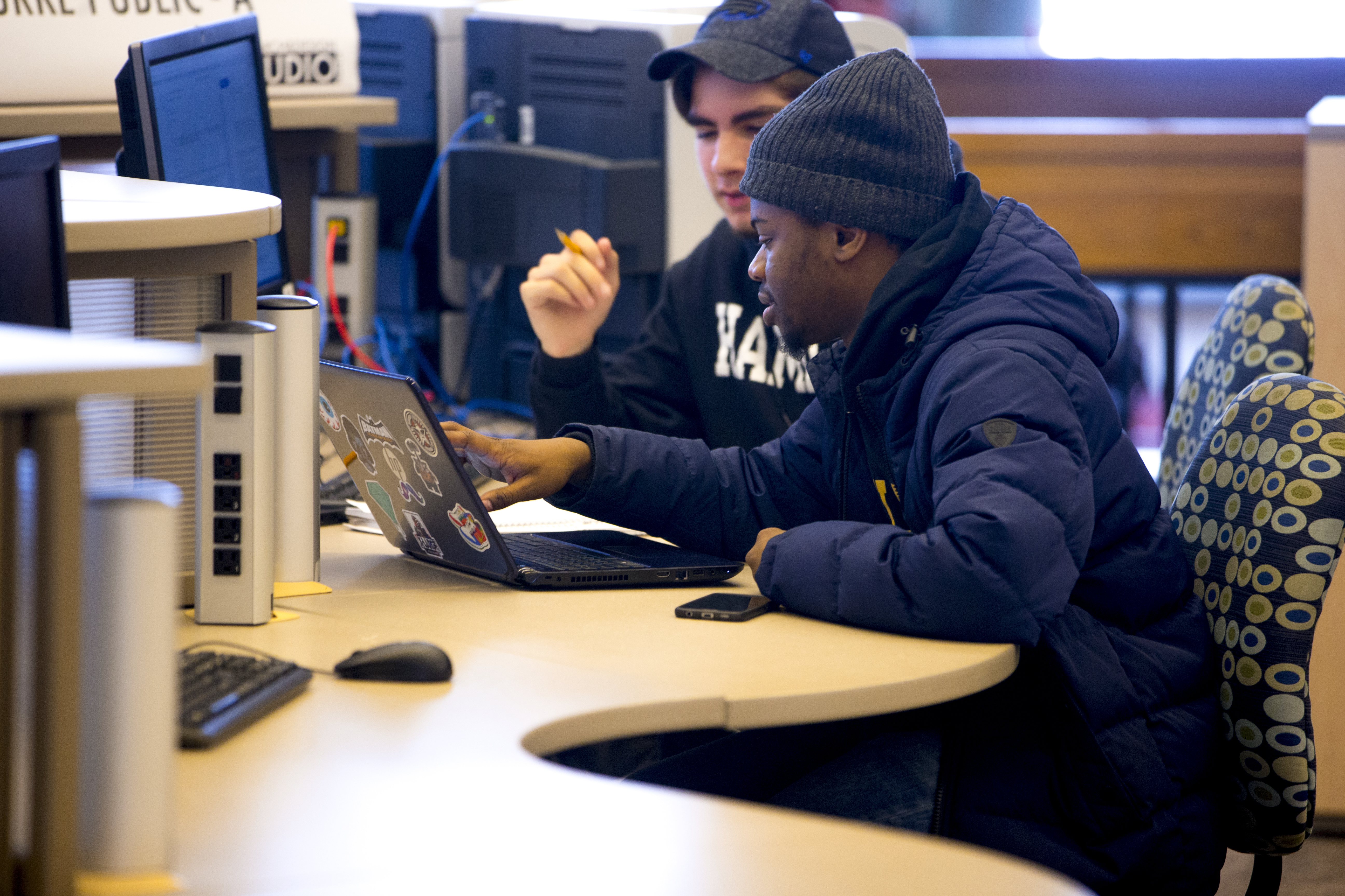 Two students studying together at a computer station in the library. One is pointing to something on their laptop screen while the other looks on.